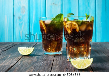 Homemade Cuba Libre with fresh lime, brown rum and crushed ice on an old wooden table. Photo stock ©