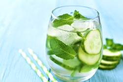 Homemade cucumber and mint lemonade in a glass on a blue wooden background.