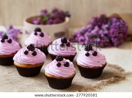 Homemade cupcakes traditional American sweet baked dessert with berries and lilac on vintage textile background. Natural light, rustic style.