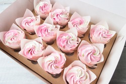 Homemade  cupcakes  with pink and white cream in a box for cakes.