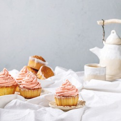 Homemade cupcakes with pink buttercream and coconut flakes served with ceramic teapot, cup of tea on white folded tablecloth.