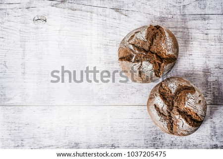 Homemade dark baked buns on wooden white table. Top view of small rolls of tasty bread.