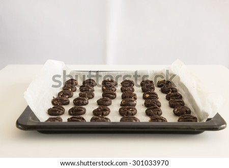 Homemade dark chocolate cookies with sweet bitter taste and have generous almond and chocolate chips.  The freshly baked cookies are still in oven tray placed on a white table and white background.