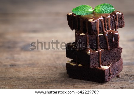 Homemade dark chocolate fudge brownies cake topping with almond slices and mint stacked on wood table with copy space. Delicious bitter sweet and fudge. Brownie is one type of chocolate cake.