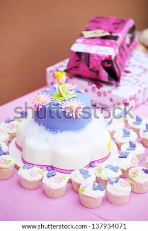 Homemade decorated birthday cake and cupcakes