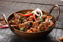 Homemade delecious mutton roast with Indian spices,,Rustic wooden background,Selective focus photograph