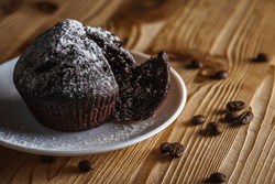 Homemade delicious chocolate muffin, pastries, buns on a white bowl on a wooden surface, close up. The concept of delicious pastries