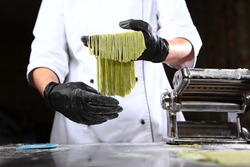 Homemade dough with spinach. The chef holds in her hands a freshly cooked spaghetti from dough with the addition of spinach.Useful ingredient. Unrecognizable person. Machine for making pasta at home.