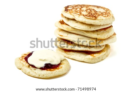 Homemade drop scones or pancakes with clotted cream and jam.