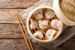 Homemade dumplings dim sum with stuffed shrimp close-up in a bamboo steamer box on the table. Horizontal top view from above