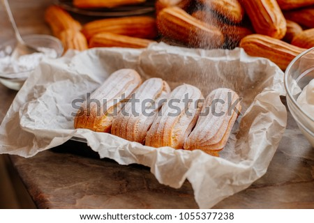 Homemade eclairs. Preparation of eclairs in the home kitchen. The process of cooking eclairs.Eclair a small, soft, log-shaped pastry filled with cream and typically topped with chocolate icing