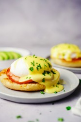 Homemade  Egg Benedict with perfect poached eggs Canadian bacon topped with Hollandaise sauce, selective focus