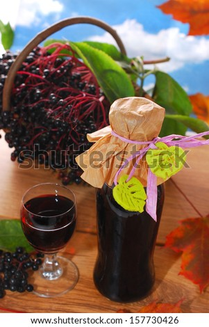 homemade elderberry juice or wine and fresh fruits in the basket