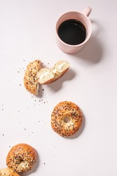 homemade everything bagels on a pink background with a cup of coffee