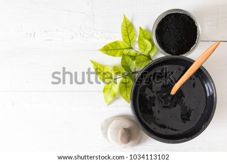 Homemade facial mask and scrub by activated charcoal powder and yogurt on white wooden background