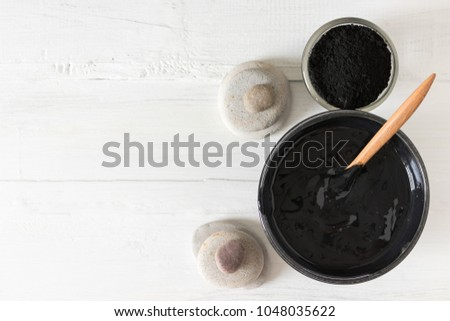Homemade facial mask and scrub by activated charcoal powder and yogurt on white wooden background #1048035622