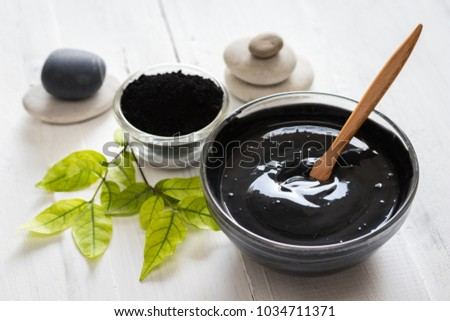 Homemade facial mask and scrub by activated charcoals powder and yogurt on white wooden background