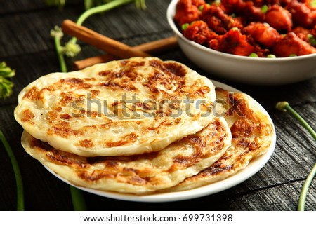 Homemade famous Indian bread paratha with meat curry.