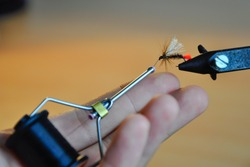 Homemade fly for fly fishing. Equipment for tying with hooks. Red Butt - Salmon fly tying. Brown wooden table as a background.