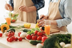 Homemade food. Happy couple at home preparing together yummy dinner for family lunch, enjoying cooking process, caring for health, eating fresh vegetable salad, cropped, close up, free space