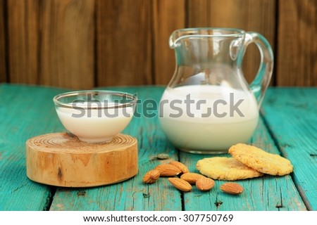Homemade fresh almond milk in glass jar and glass bowl, with homemade almond cookies and whole almonds on shabby turquoise wooden table