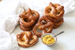 Homemade freshly baked delicious Pretzels against white background served with mustard . Top view, copy space. Oktoberfest, Pretzel day, Bavarian, Alsatian typical bread.