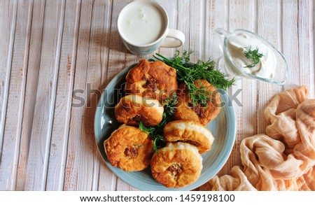 Homemade fried dough with minced meat or belyashi. Pies are on a plate on a white wooden table. Top view. Copy space. #1459198100