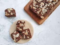 Homemade fudge brownie with almond slices and choco chip on top served on wooden board on white texture background. Selective focus
