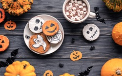 Homemade funny spooky cookies pumpkins ghosts bats spiders and cocoa with marshmallow on brown wooden table background, trick or treat holiday decor, top view, happy Halloween concept, copy space