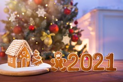 Homemade gingerbread house on the background of a decorated Christmas tree and unfocused lights with a masked man cookies, and numbers of new year