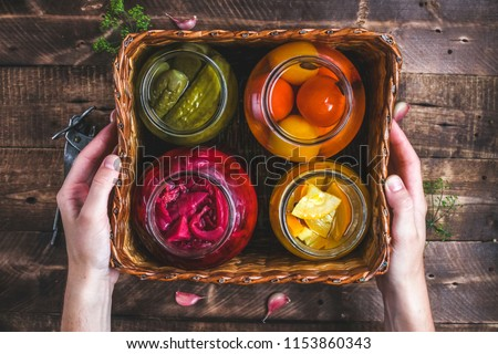 Homemade glass jars of pickled fresh cucumbers, juicy tomatoes, sweet zucchini in a wicker box on a wooden background. Stock of food. Autumn concept. Top view #1153860343