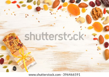 Homemade gluten free granola bars and mixed nuts, seeds, dried fruits on white wooden background. Copyspace background.Top view.
