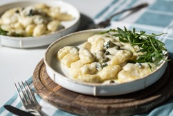 Homemade gnocchi with creamy gorgonzola sauce, capers and arugula in white plate on wooden board.