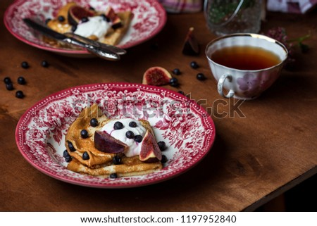 Homemade golden crepes with fresh figs blueberries and sour cream #1197952840