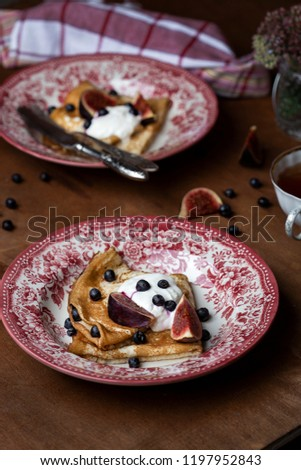 Homemade golden crepes with fresh figs blueberries and sour cream #1197952843