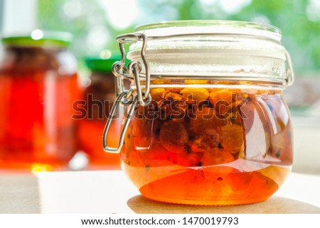 Homemade gooseberry jam in a glass jar isolated in sunlight. Close up.
