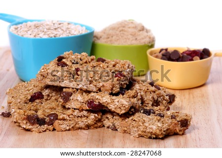 Homemade granola bars with ingredients in measuring cups in the background