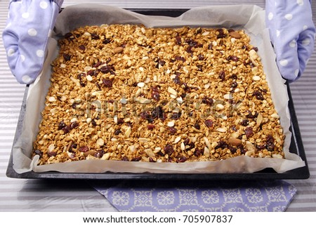 Homemade granola from oat flakes, almonds, honey, bananas and almonds on a baking sheet.  #705907837