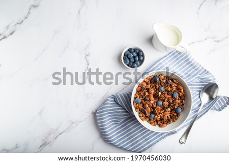 Homemade granola, muesli with pieces of dark chocolate, nuts and blueberries in bowl on white marble background. Healthy breakfast. Top view. Space for text. Foto stock ©