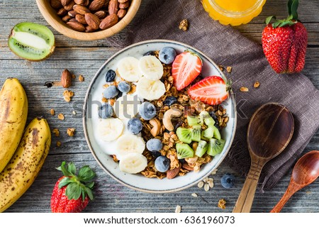 Homemade granola with nuts and raisins, kiwi, blueberries, banana, strawberries and plain yogurt. Top view. Concept of healthy lifestyle, dieting, healthy eating and breakfast
