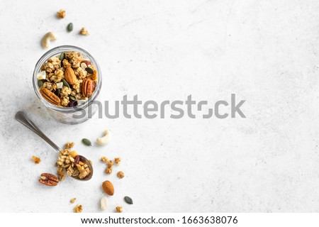 Homemade granola with nuts and seeds in glass jar. Organic granola for healthy breakfast on white, top view, copy space. Stockfoto ©