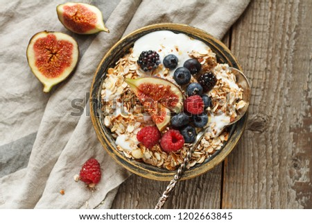Homemade granola with yogurt, figs and berries on wooden background. Healhty breakfast. Top view Foto d'archivio ©