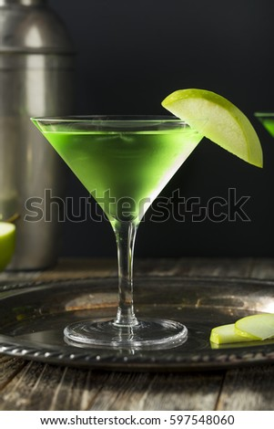 Homemade Green Alcoholic Appletini Cocktail with Apple Garnish #597548060