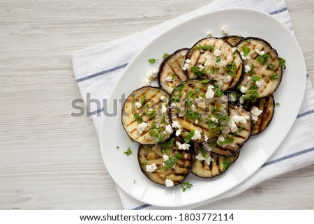 Homemade Grilled Eggplant with Feta and Herbs on a white plate, top view. Flat lay, overhead, from above. Copy space. Сток-фото ©