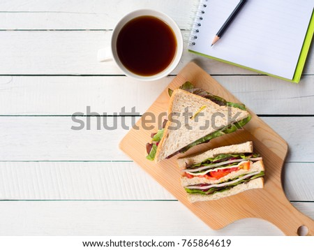 Homemade ham cheese sandwich and coffee cup for breakfast on white working desk in top view with copy space.