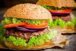 homemade hamburger close up with fresh green lettuce, tomato and red onion