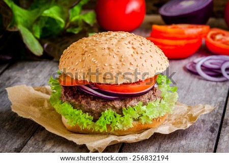 homemade hamburger close up with fresh green lettuce tomato and red onion on rustic background