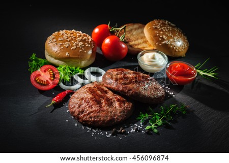 Homemade hamburger. Grilled beef patties, sesame buns with other ingredients on dark slate plate