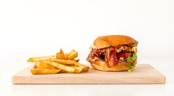 Homemade hamburger on a cutting board with fries.