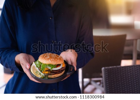 Homemade hamburger served on rustic plate, waitress serving in hands  #1118300984